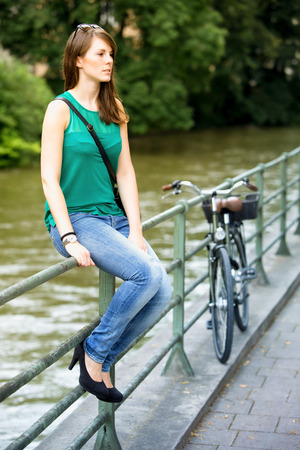 young brunette woman sitting on railing by river and waiting