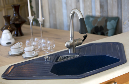 tabel: close up of blue kitchen sink and dining room table with dishes