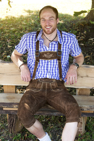lederhosen: young man sitting on bench in traditional bavarian clothes smiling at camera