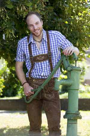 tracht: handsome man in traditional bavarian clothes standing next to an old water pump Stock Photo