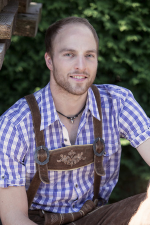 lederhosen: portrait of handsome young man outdoors in traditional bavarian clothes