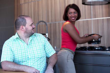 hombre con sobrepeso sentado en la mesa de la cocina y la mujer hispana está cocinando Foto de archivo