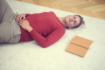 Biondo biondo sdraiato sul tappeto con un libro