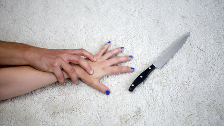 rapist: hand of woman trying to grab a knife while being attacked by man