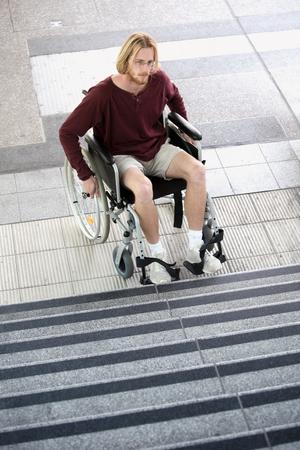 paraplegico: joven sentado en la silla de ruedas delante de las escaleras y mirando triste Foto de archivo