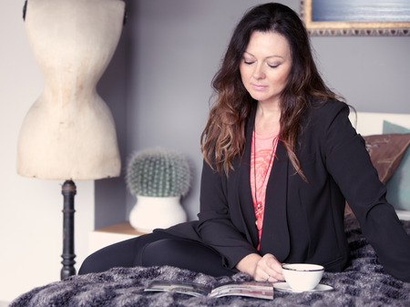 tea cosy: brunette woman sitting on bed, reading a magazine and drinking coffee