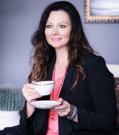 tea cosy: beautiful brunette woman sitting in living room and drinking coffee Stock Photo