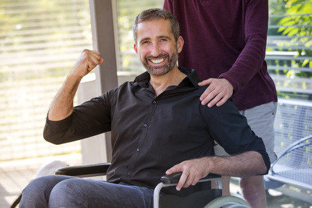 handsome man in wheelchair looking at camera and looking very optimistic Stock Photo