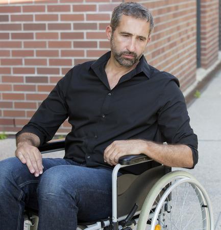 Knappe man zittend in een rolstoel en op zoek depressief Stockfoto - 65214390