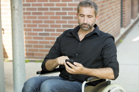 impaired: handsome man in wheelchair texting on his phone