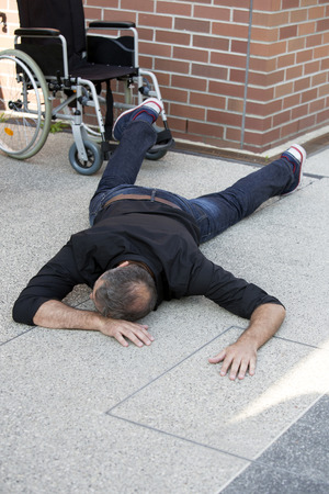 crippled: impaired man lying on street after in fell out of wheelchair