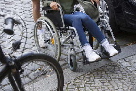 disablement: closeup of woman in wheelchair getting help to reach the sidewalk