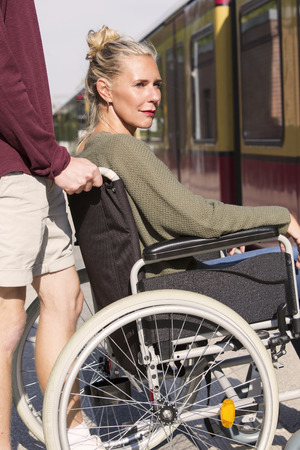 immobility: woman in wheelchair at train station with someone helping her Stock Photo