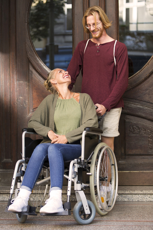 woman in wheelchair at an entrance with a young man helping her Stock Photo