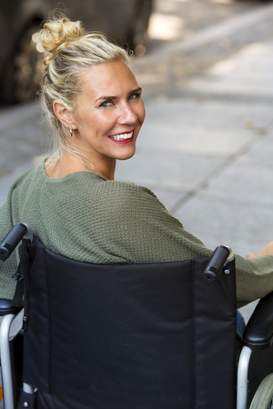woman in wheelchair outdoors smiling at camera Stock Photo
