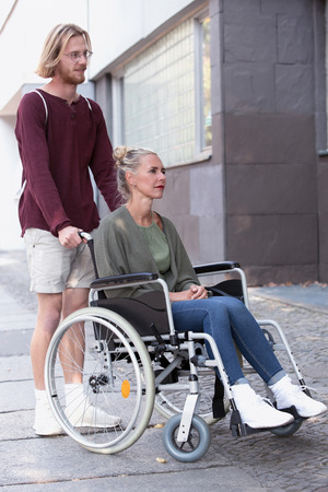 immobility: woman in wheelchair on the sidewalk and young man helping her