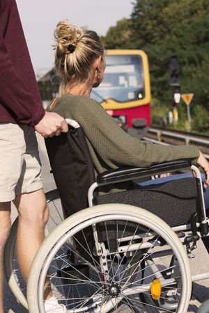 immobility: woman in wheelchair at a train station with someone helping her Stock Photo