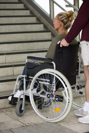 immobility: woman in wheelchair in front of stairs outside