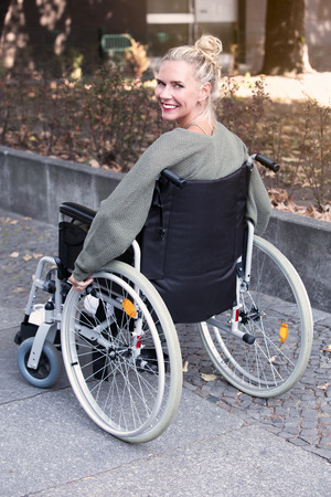 woman in wheelchair at sidewalk smiling at camera Stock Photo