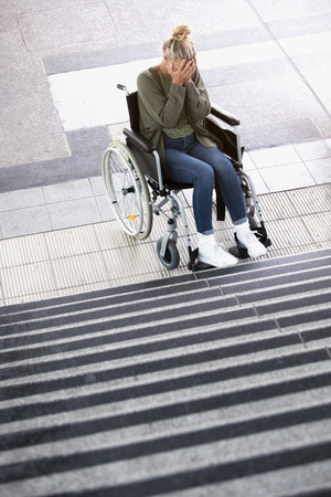 immobility: woman in wheelchair in front of stairs outdoors  looking desperate Stock Photo