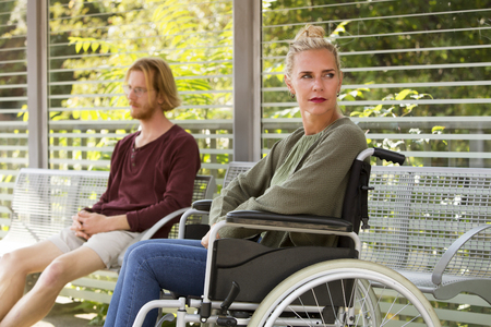 disablement: woman in wheelchair outdoors next to young man sitting on bench Stock Photo
