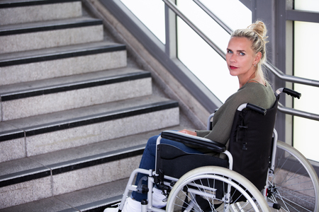 immobility: woman in a wheelchair in front of stairs outside