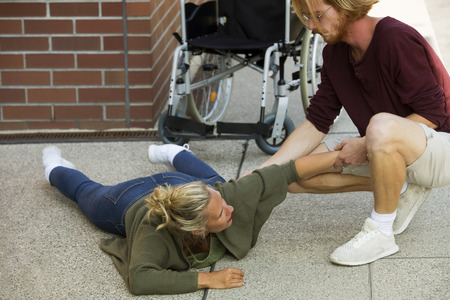 immobility: disabled woman lying on floor next to wheelchair and getting help from young man