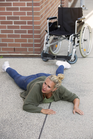 immobility: woman lying on floor on pavement next to a wheelchair Stock Photo