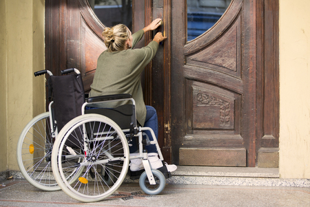 immobility: woman in wheelchair in front of entrance door trying to get in Stock Photo
