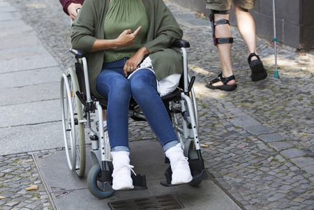 disablement: closeup of woman in a wheelchair pointing to another disabled person