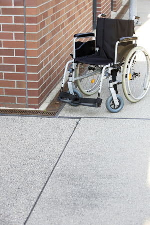 immobility: wheelchair standing by a brick wall on a sidewalk