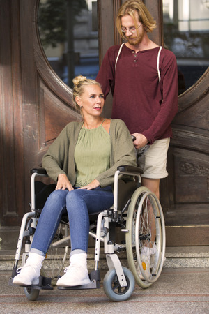 disablement: woman in wheelchair in front of an entrance and a young man helping her Stock Photo