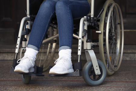 disablement: closeup of woman in a wheelchair in front of an entrance