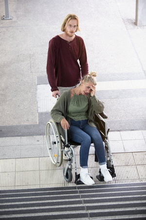 disablement: woman in wheelchair in front of stairs outside