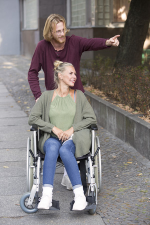 woman in wheelchair on sidewalk and young man showing her something
