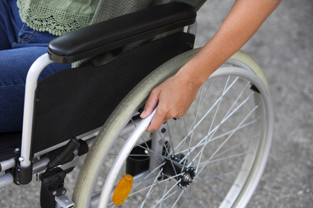 immobility: closeup of woman sitting in a wheelchair outside