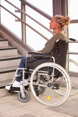woman in a wheelchair in front of stairs outside