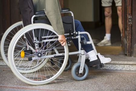 immobility: closeup of woman in wheelchair in front of an entrance door