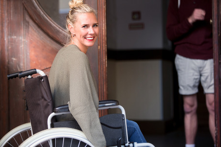 invalidity: blond woman in wheelchair in front of entrance and man holding the door