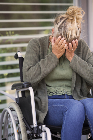 immobility: blond woman in wheelchair outdoors crying