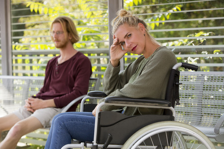 immobility: woman in wheelchair outside next to young man sitting on bench