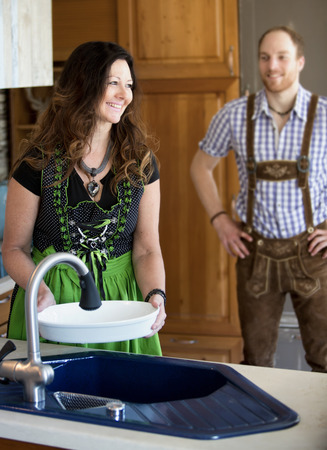tracht: couple in traditional bavarian clothes standing in kitchen and smiling
