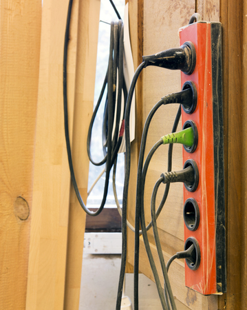 sockets: old sockets with a bunch of cables hanging on wall