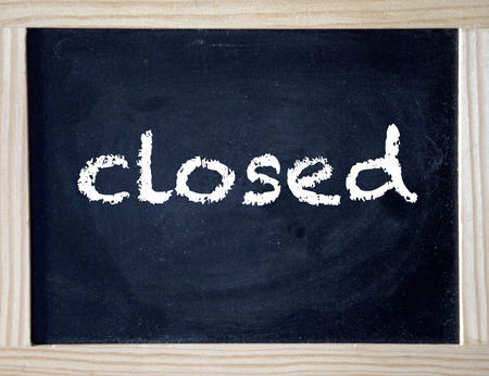 the word closed written on black chalkboard Stockfoto