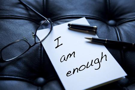 Ik ben genoeg geschreven op papier naast pen en bril op zwart leer Stockfoto - 69769909