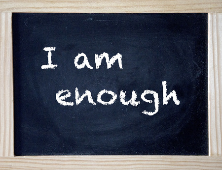 the words I Am Enough written on black chalk board