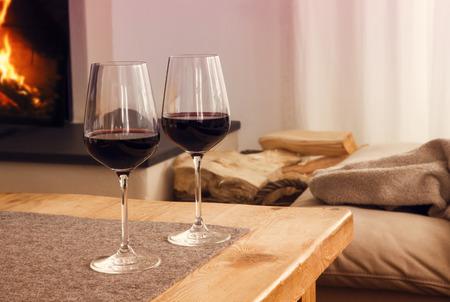 close-up van twee glazen met rode wijn op tafel in de woonkamer met open haard op de achtergrond