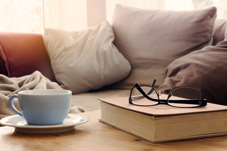closeup of cup and book with eyeglasses on wooden table in front of couch in living room Stock Photo
