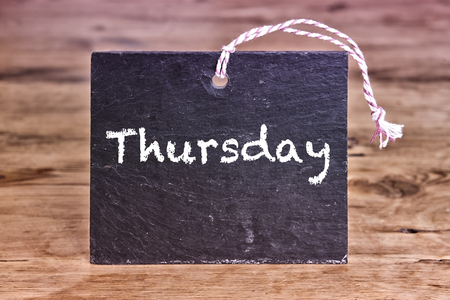 thursday: the word Thursday written on chalk board on wooden table Stock Photo