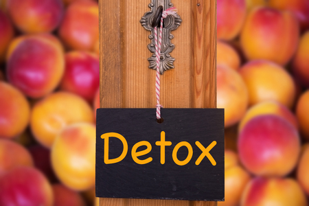small blackboard with the word Detox hanging on key in front of peaches